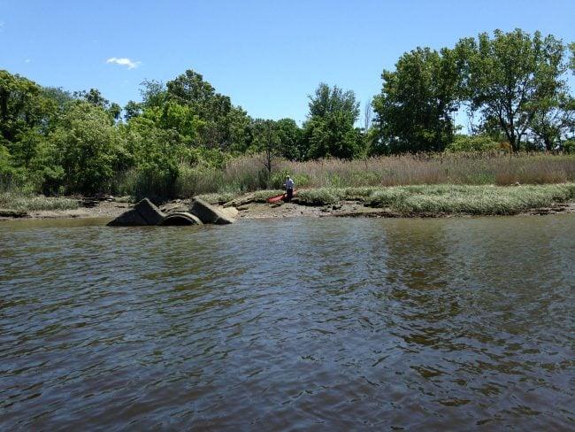 A fisherman beside a huge pipe on the Westchester Creek. (Photo by Dan Shapley / Riverkeeper)