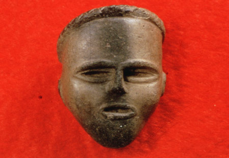 Clay effigy face, likely once attached to a tobacco pipe